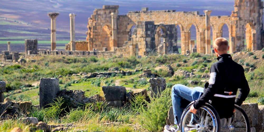man in wheelchair with roman ruins in the background