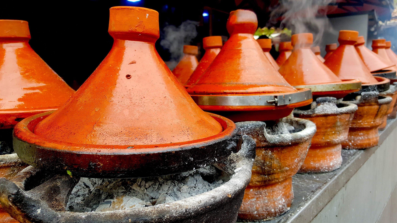 Tajines, traditional ceramic dish, slowly cooking over fresh coals