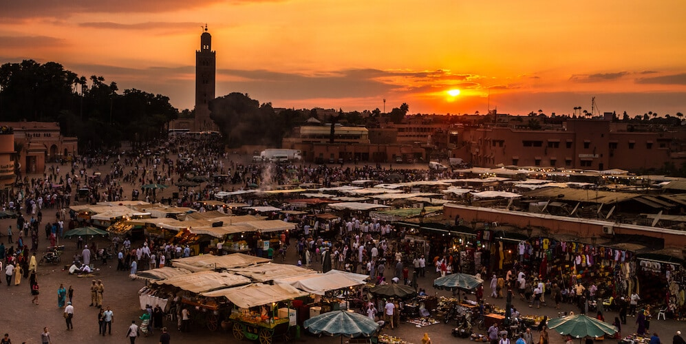 Orange sunset behind the bustling main square of Marrakech