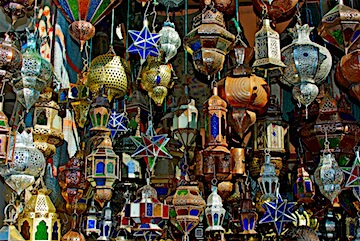 A variety of traditional Moroccan decorative chandelier lamps hanging from a shop's ceiling