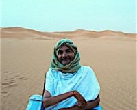 Man in wheelchair smiling in the Sahara