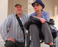 Man kneeling next to woman in wheelchair
